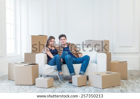 Moving home and relocation of a new life. Couple in love pulls things out of boxes for moving while man and woman sitting among the boxes in an empty apartment