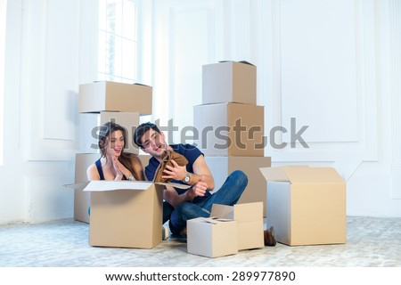 Moving home and repair of a new life. Couple in love pulls things out of boxes for moving while man and woman sitting among the boxes in an empty apartment