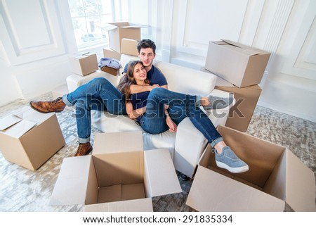 Moving home and repair of a new life. Couple in love pulls things out of boxes for moving while man and woman sitting among the boxes in an empty apartment - stock photo