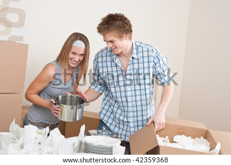Moving house: Young couple unpacking kitchen dishes, pots, pans, in new home - stock photo