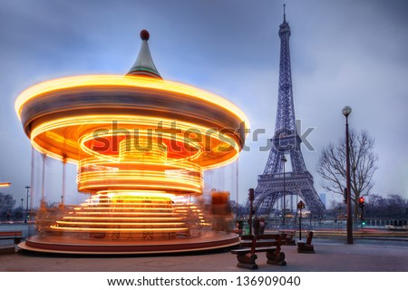 moving illuminated vintage carousel close to Eiffel Tower, Paris