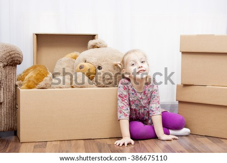 moving in the new home, cute girl and her teddy bear - stock photo