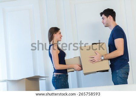 Moving new flat with fun and excitement. Young and beautiful couple is moving to new apartment surrounded with plenty of  boxes. Both are holding packs with their clothes while moving new apartment