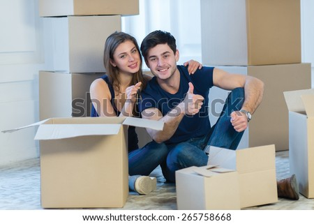Moving new flat with fun and excitement. Young and beautiful couple is moving to new apartment surrounded with plenty of boxes. Both are sitting on the floor and holding keys for their new cozy house - stock photo