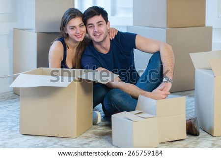 Moving new flat with fun and excitement. Young and beautiful couple is moving to new apartment surrounded with plenty of cardboard boxes. Both are sitting on floor and dreaming about new cozy house - stock photo