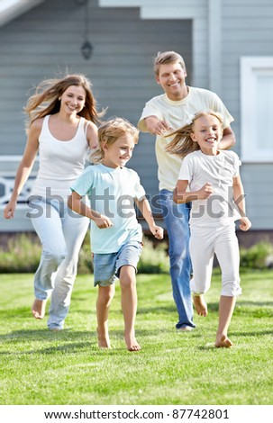 Moving parents and children in the garden - stock photo