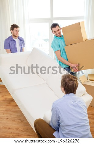 moving, real estate and friendship concept - smiling male friends with sofa and boxes at new home - stock photo