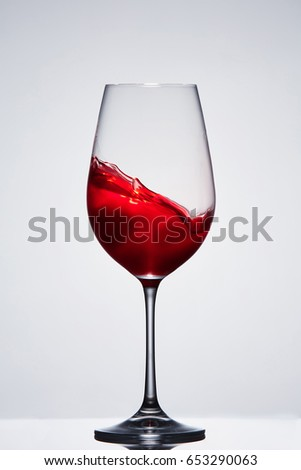 Moving red wine in the elegant wineglass standing against light background with reflection.