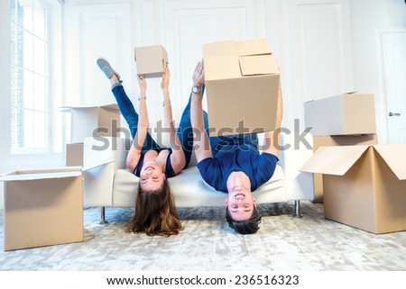 Moving, repairs, new apartment. Couple girl and the guy keep moving boxes in hands and looking at the camera while man and woman lying on the sofa among the boxes in an empty apartment