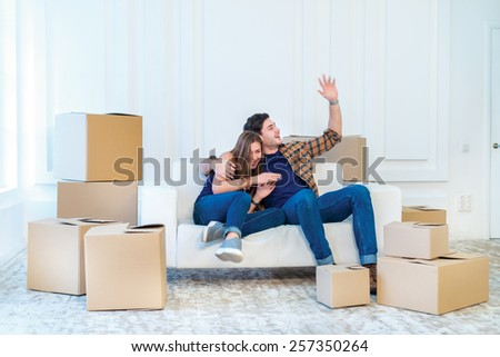Moving, repairs, new flat. Couple girl and guy lie on the floor in the arms and showing okay thumbs up while man and woman lying on the floor among the boxes in an empty apartment view from above - stock photo