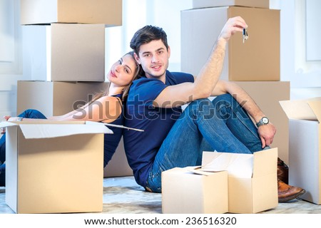 Moving, repairs, new house keys. Couple girl and the guy holding the keys to the apartment while man and woman sitting on the floor among the boxes in an empty apartment - stock photo