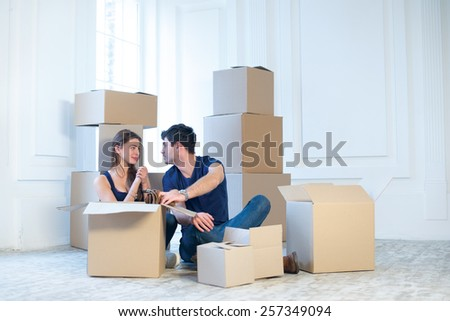 Moving, shifting to a new house and repairs in the apartment. Love couple sitting on a floor and hugging while a young and beautiful couple in love sitting in an empty apartment among boxes