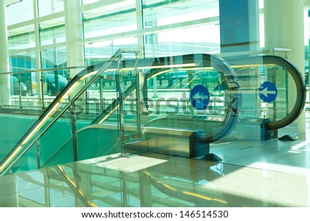 Moving staircase in the airport in concrete and glass building - stock photo