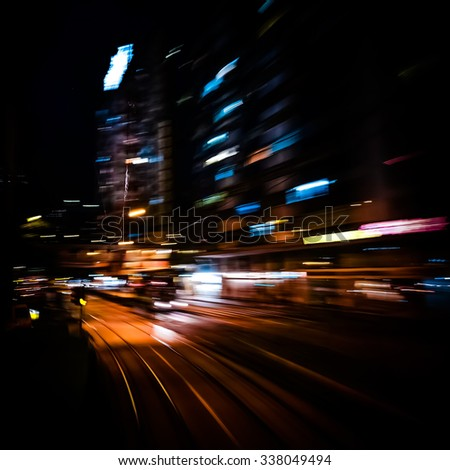 Moving through modern city street with illuminated skyscrapers. Hong Kong.Abstract cityscape traffic background with motion blur, art toning - stock photo