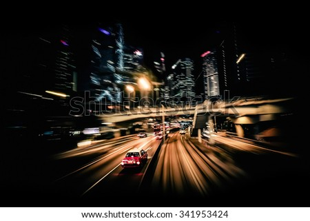 Moving through modern city street with illuminated skyscrapers. Hong Kong. Abstract cityscape traffic background with taxi car driving at night. Motion blur, art toning - stock photo