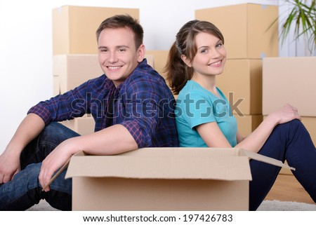 Moving to a new apartment. Beautiful young couple standing close to each other and smiling at camera while holding cardboard boxes