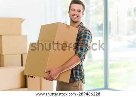 Moving to a new apartment. Cheerful young man holding a cardboard boxes and smiling at camera while other carton boxes laying on background - stock photo