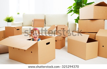 moving to a new apartment. happy child in a cardboard box - stock photo