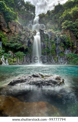 Moving water at the beautiful Trois Bassins waterfall as it plunges into a blue lagoon on Reunion Island. - stock photo