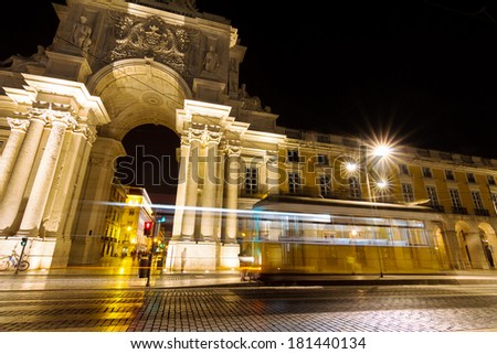 Moving yellow tram in front of the gate at the commerce square at night in Lisbon, Portugal - stock photo