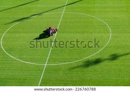 Mowing grass on the football stadium - stock photo
