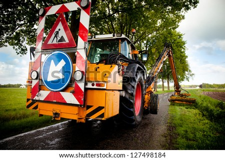 mowing grass shoulder with machine  along roadside - stock photo