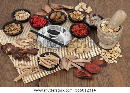 Moxa sticks and chinese herbs used in traditional herbal medicine with mortar and pestle over bamboo and oak background. - stock photo
