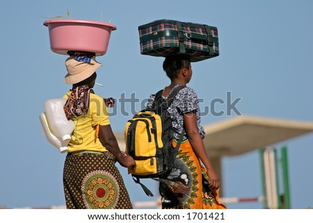 Mozambican woman in traditional dresses carrying their luggage on their heads - stock photo