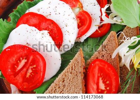 mozzarella and tomato slices on wooden plate - stock photo
