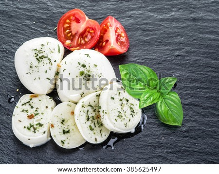 Mozzarella and tomatoes. Dark grey background.