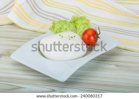 Mozzarella cheese in the bowl on the wooden background