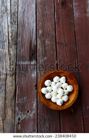 Mozzarella cheese in wood bowl on rustic wooden background, top view - stock photo