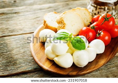 mozzarella cheese on a dark wood background. tinting. selective focus on Basil - stock photo