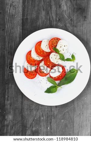 Mozzarella cheese tomato and basil on a plate - stock photo