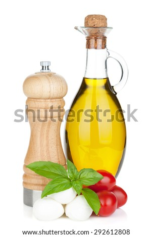 Mozzarella cheese with cherry tomatoes, basil and olive oil with pepper shaker. Isolated on white background - stock photo