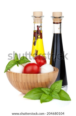Mozzarella cheese with cherry tomatoes, basil and olive oil with vinegar. Isolated on white background - stock photo