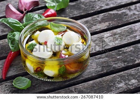 Mozzarella marinated with garlic, spices and basil in olive oil.Selective focus. - stock photo