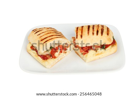 Mozzarella, pancetta, tomato and basil pannini cut in half on a plate isolated against white - stock photo