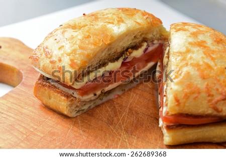 Mozzarella sandwich/sliced ciabatta filled with tomato, mozzarella & red onion slices on rustic wood serving board - stock photo