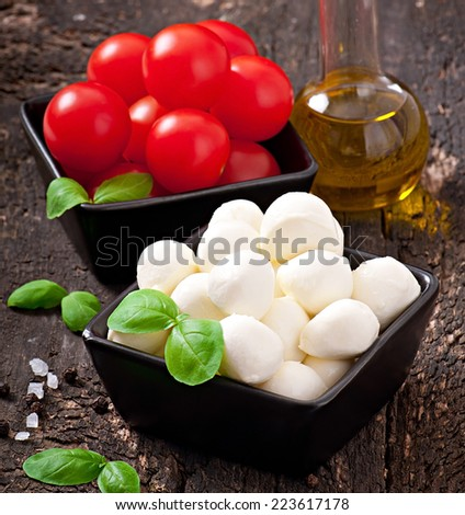Mozzarella, tomatoes and fresh basil leaves on wooden background - stock photo