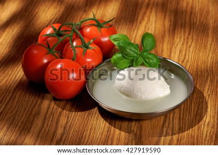 Mozzarella, tomatoes, basil, composition on a wooden table - stock photo