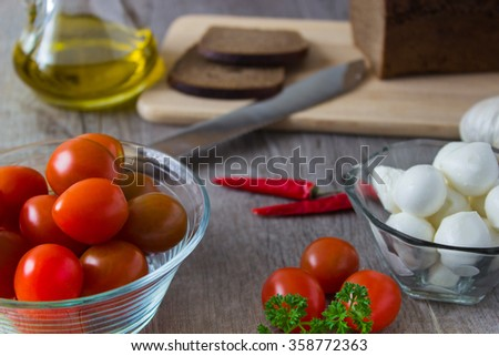Mozzarella, tomatoes, bread on wooden board.