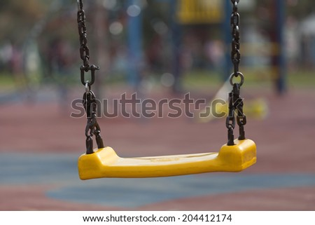 mpty yellow plastic swings on modern playground with shallow depth of field - stock photo