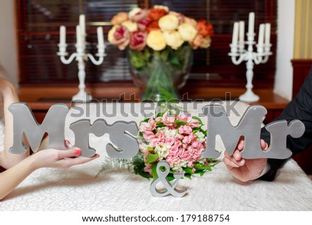 Mr. and Mrs. words in the hands of the bride and groom beautiful wedding decor handmade - stock photo