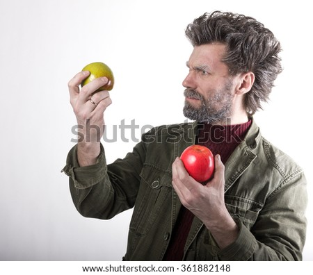 Mr. IceMan, smiling man with a beard, beard covered with hoarfrost, man holding apples, he stares at them. fashion man in knitted sweater and jacket.  - stock photo