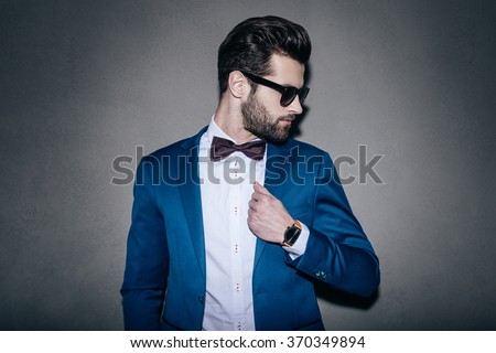 Mr. Perfection. Close-up of handsome young man wearing sunglasses adjusting his jacket and looking over his shoulder while standing against grey background - stock photo