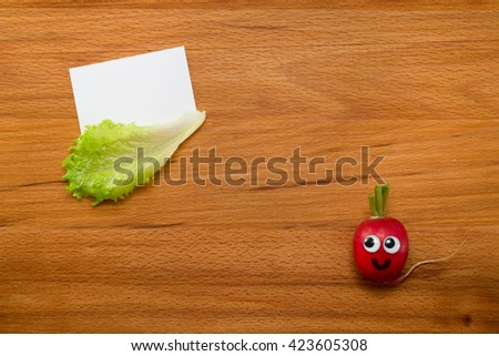 Mr. Radish is smiling and looking at the blank card, next are the lettuce on wooden table. Close-up view from above - stock photo