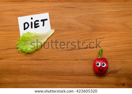 Mr. Radish is smiling and looking at the card with the word 'DIET', next are the lettuce on wooden table. Close-up view from above - stock photo