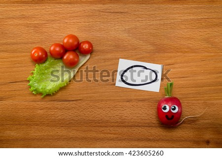 Mr. Radish is smiling and looking at the lettuce and cherry tomatoes on wooden table. Close-up view from above - stock photo