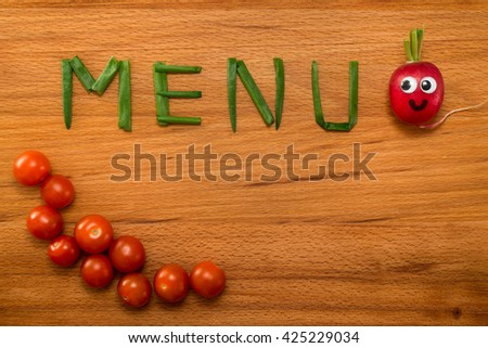 Mr. Radish is smiling and looking at the onion petals folded in the form of the word 'MENU' and cherry tomatoes on wooden table. Close-up view from above - stock photo